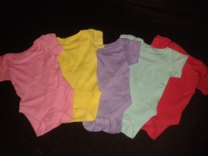 Five baby vests, assorted colours.